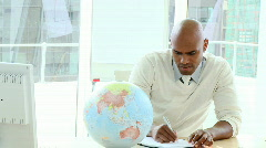 Positive ethnic businessman looking at a terrestrial globe Stock Footage