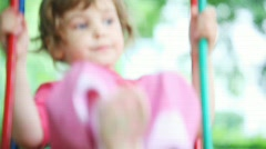 Little girl blonde in pink t-shirt teeter in park close Stock Footage