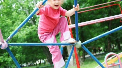 Little girl blonde in pink clothes climbs on iron rod on children's playground Stock Footage