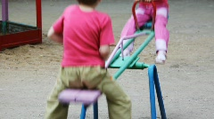 boy and girl play at seesaw together on playground - stock footage