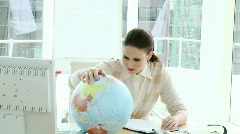 Pretty businesswoman looking at a terrestrial globe - stock footage