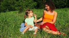 Mother and daughter sits on lawn near forest and eats sweet cherry Stock Footage