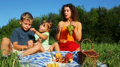 Mother daughter and son sits on lawn near forest and eats vine Stock Footage