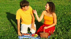 Couple sits on green lawn and feed each other with fruit, vine and cherry Stock Footage