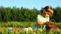 Girl sits on lawn in grass, eats cherry and spits out stones Stock Footage