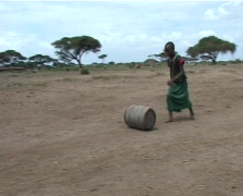 Girl rolling jerry can of water Stock Footage