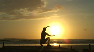 Woman meditating at sunrise on a beach Stock Footage