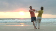 Stock Video Footage of Couple dancing at sunrise on a beach