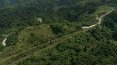 Aerial following slightly winding road through rain forest area with hills Stock Footage