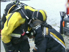 Firefighter scubadiver coming out of the water Stock Footage