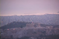Telephoto of the Parthenon atop the acropolis at dusk with sea in background in Stock Footage