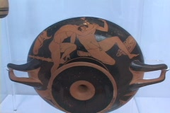 Red figure pottery bowl showing nude, wrestling athletes Stock Footage