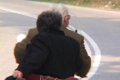Old man, old woman on motorcyle, vespa, scooter Stock Footage