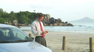 Stock Video Footage of Businessman talking on cell phone beside his car on a beach
