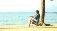 Stock Video Footage of Man reading a book on a beach