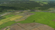 Aerial over rural fields with a river going right through Stock Footage