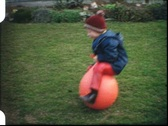 Stock Video Footage of Boy hopping on ball (vintage 8 mm amateur film)