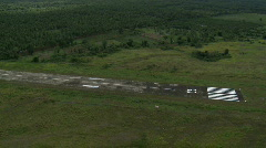 Aerial approaching a concreted and marked airstrip in a rural area - stock footage