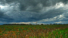 Motion time lapse of heavy clouds over cropped fields - hdri Stock Footage