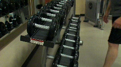 Dumbells being picked up off the rack NTSC Stock Footage
