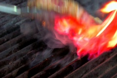 Chef cooking a thick rib steak on flaming grill - stock footage