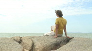 Woman relaxing on a rock at the sea Stock Footage