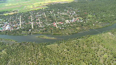Aerial following a river through rural area with village and plantations Stock Footage