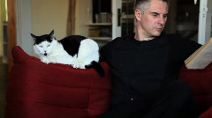 Man reading on couch with cat Stock Footage