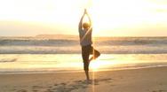Businessman doing yoga on a beach Stock Footage