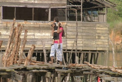 Women with child walking in a kampung village on Batam Island Indonesia Stock Footage