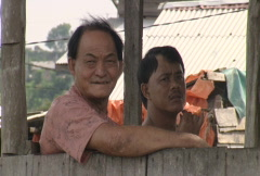 Batam harbour men sitting in a shed  Stock Footage
