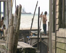 Batam harbour man with his boat Stock Footage