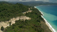 Aerial along a rough coastal road through the forest with erosion showing in the Stock Footage