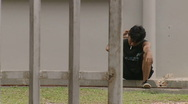 Stock Video Footage of Batam Indonesia detainee smoking a cigarette behind bars