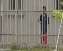 Batam Indonesia detainee behind prison bars  - stock footage