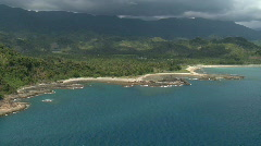 Aerial from the sea side of a tropical beach with jungle and mountains in the Stock Footage
