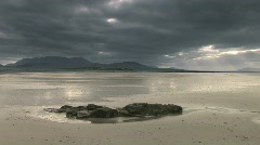 Clouds rush overhead a rocky sandy beach Stock Footage