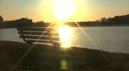 Sunset on lake in front of bench Stock Footage