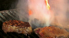 Juicy steaks sizzle on flaming and smoking grill - stock footage