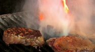 Stock Video Footage of Juicy steaks sizzle on flaming and smoking grill