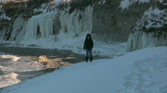 Filipina woman walking on a snow covered beach in Sweden Stock Footage