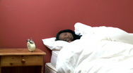 Stock Video Footage of Afro-American woman in her bed looking at the alarm clock
