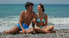 Woman and man with sea stars sits on pebble beach, sea in background Stock Footage