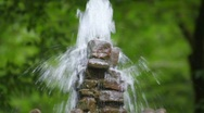 Fountain in forest, panning downwards, close-up, trees in background Stock Footage