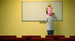 Man holding little girl on shoulders cleans whiteboard in lecture room Stock Footage