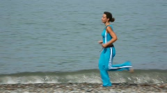 young woman in tracksuit running on pebble coast, sea in background - stock footage