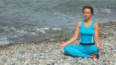 young woman in tracksuit sits in pose of lotus on pebble beach - stock footage