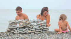 Family of three building wall of stones on beach, sea surf in background Stock Footage
