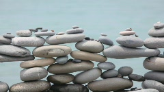 Wall of stones on beach, sea surf in background, panning downwards Stock Footage