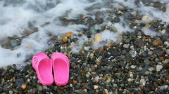 Children's pink slippers on pebble beach with sea surf Stock Footage